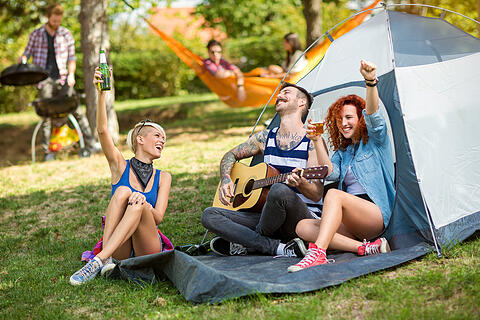 Cheerful youth drinks beer and play guitar in camp